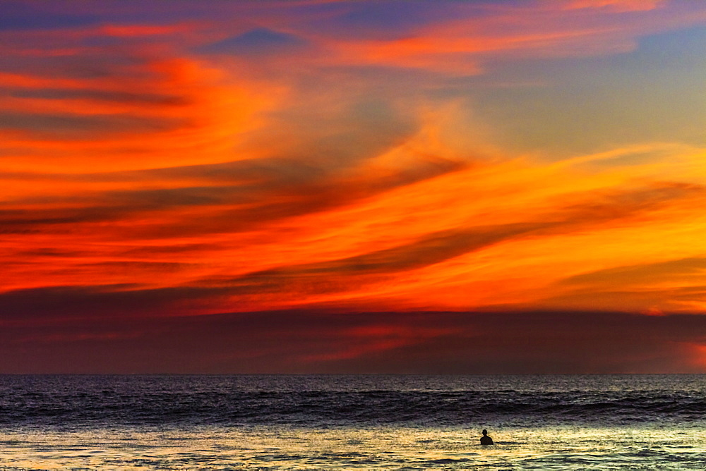 Lone surfer and sunset clouds off Playa Hermosa surf beach, southern Nicoya Peninsula, Santa Teresa, Puntarenas, Costa Rica, Central America