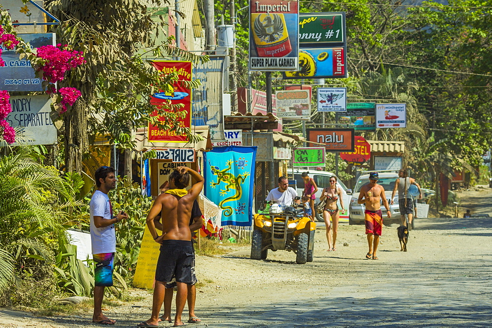 Tourists and signs on the main strip at this busy south coast of Nicoya Peninsula resort, Santa Teresa, Puntarenas, Costa Rica, Central America