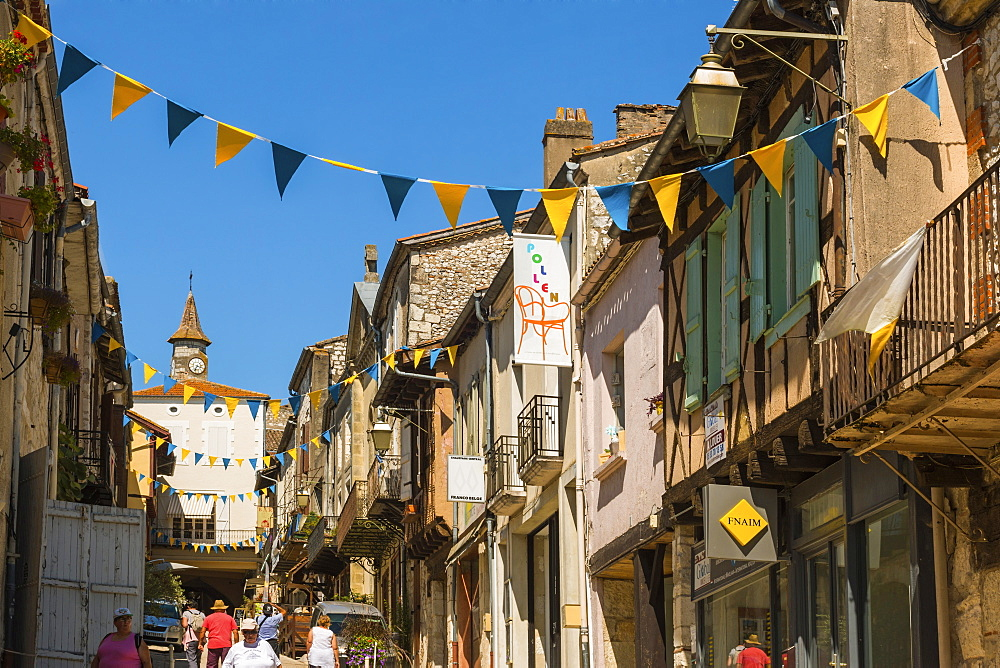 Restaurants and shops on steep Rue St. Pierre in this attractive south western bastide town, Monflanquin, Lot-et-Garonne, France, Europe