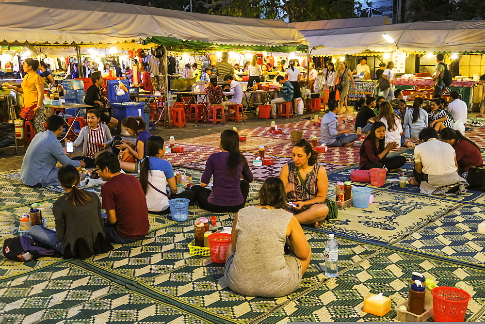 People seated on mats eating at the colourful Phsar Kandal night market near the riverfront, City centre, Phnom Penh, Cambodia, Indochina, Southeast Asia, Asia - 83-13051