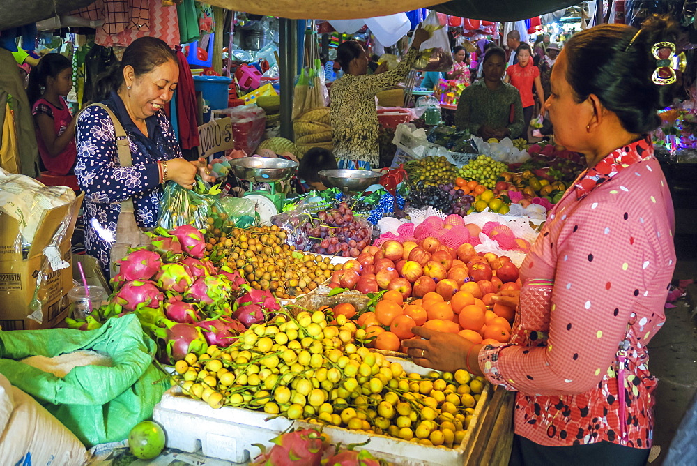 Woman shopping at a fruit stall in the central market at this old formerly French colonial river port city, Kampot, Cambodia, Indochina, Southeast Asia, Asia