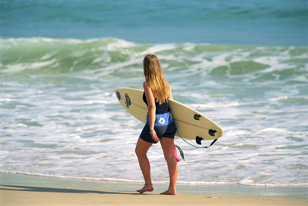 Girl carrying surfboard on beach, Byron Bay, New South Wales, Australia, Pacific