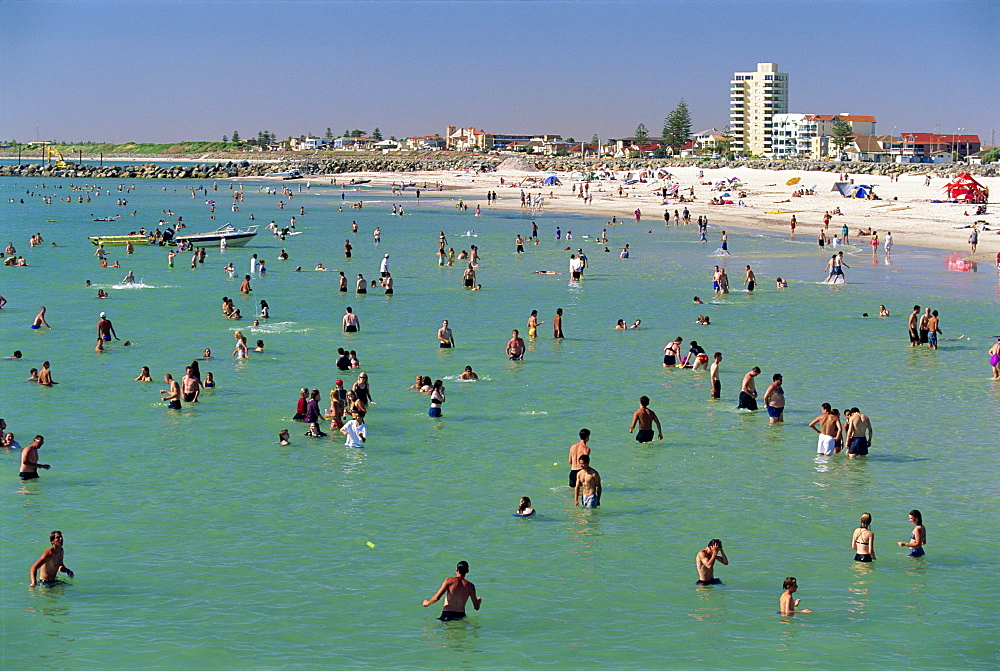 Groups of people in the sea and on the beach at Glenelg, a resort suburb of Adelaide, where first South Australian colonists landed, South Australia, Australia, Pacific