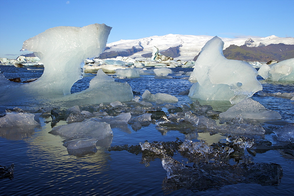 Icebergs on glacial lake at Jokulsarlon with snow on the massive icecap of Vatnajokull behind, Iceland, Polar Regions