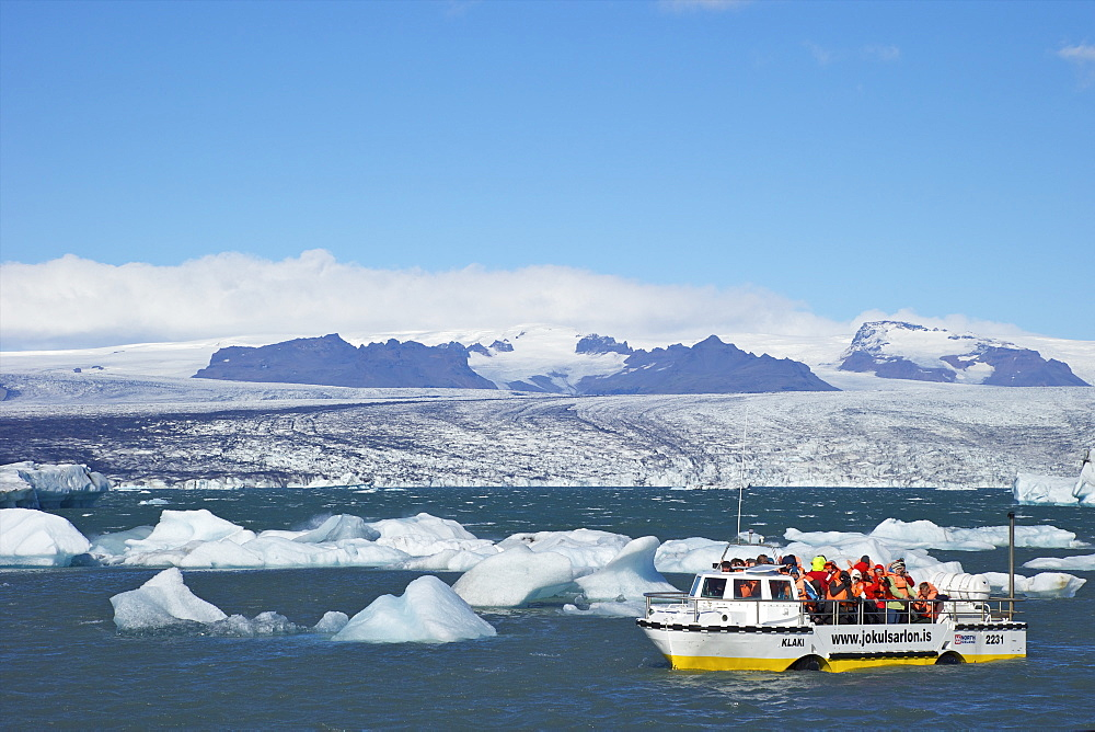 Amphibious vehicle between icebergs on glacial lake at Jokulsarlon with snow on massive icecap of Vatnajokull behind, Iceland, Polar Regions