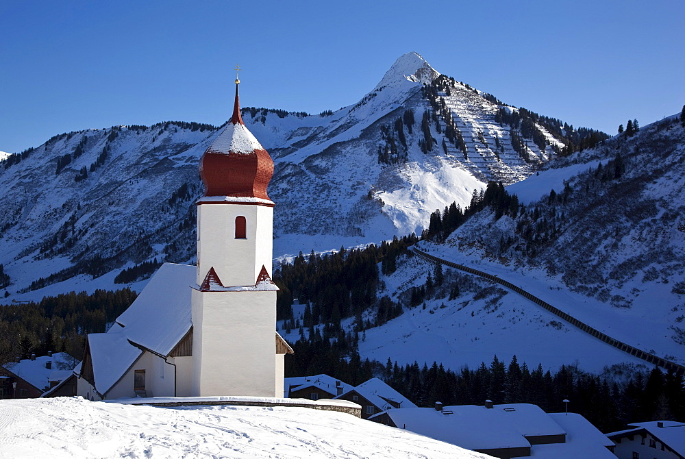 St. Nicholas, little church of Damuels with traditional bulb roof, mountains at back, Vorarlberg, Austria, Europe
