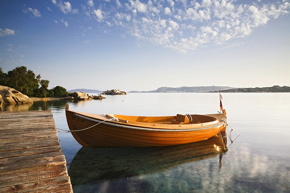 Boat being reflected in the water at dawn, Sardinia, Italy, Europe