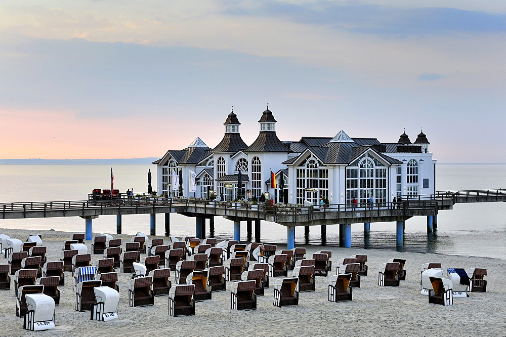 Beach chairs on the sandy beach of the Baltic resort Sellin, in the back the historic pier with restaurant, Ruegen island, Mecklenburg-Western Pomerania, Germany, Europe