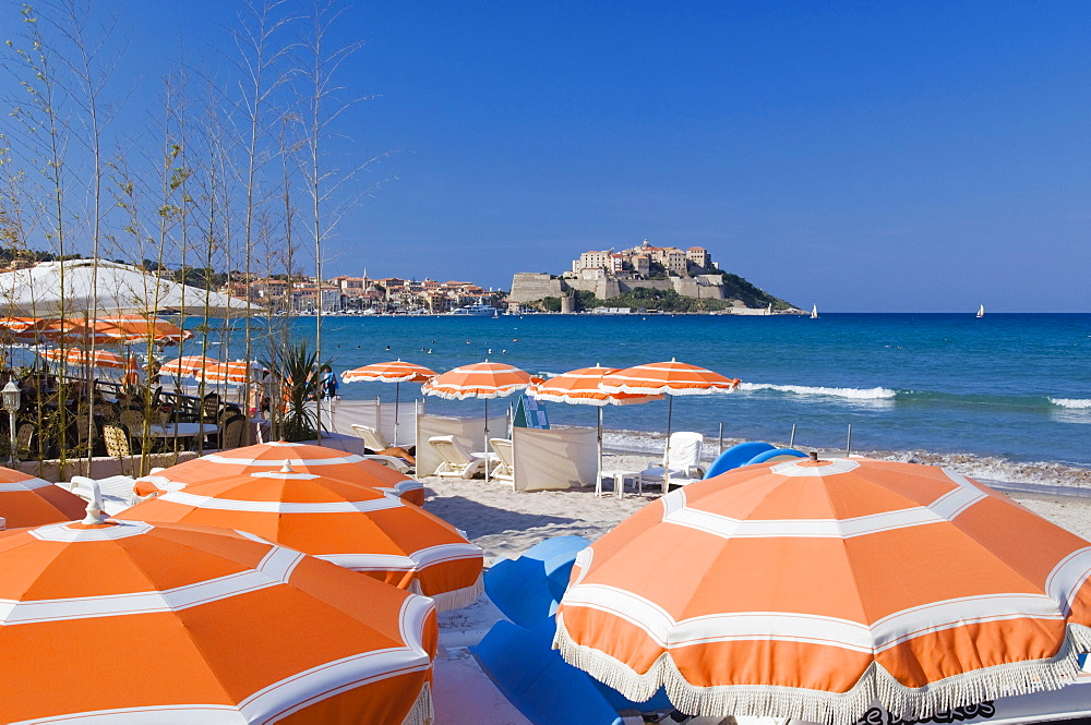 Sun umbrellas on beach, view of the citadel of Calvi, Balagne, Corsica, France, Europe