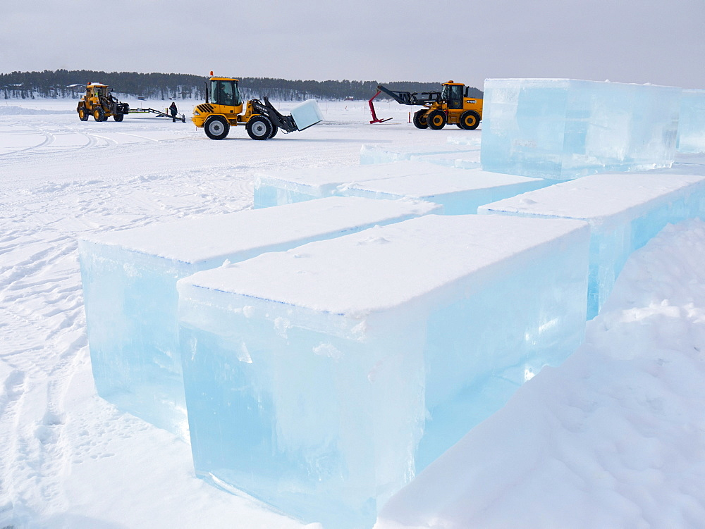 Near the ice hotel in Jukkasjaervi, large blocks of ice are cut and lifted from the frozen Torne Aelv River with heavy equipment, Jukkasjaervi, Kiruna, Lappland, northern Sweden, Sweden, Europe