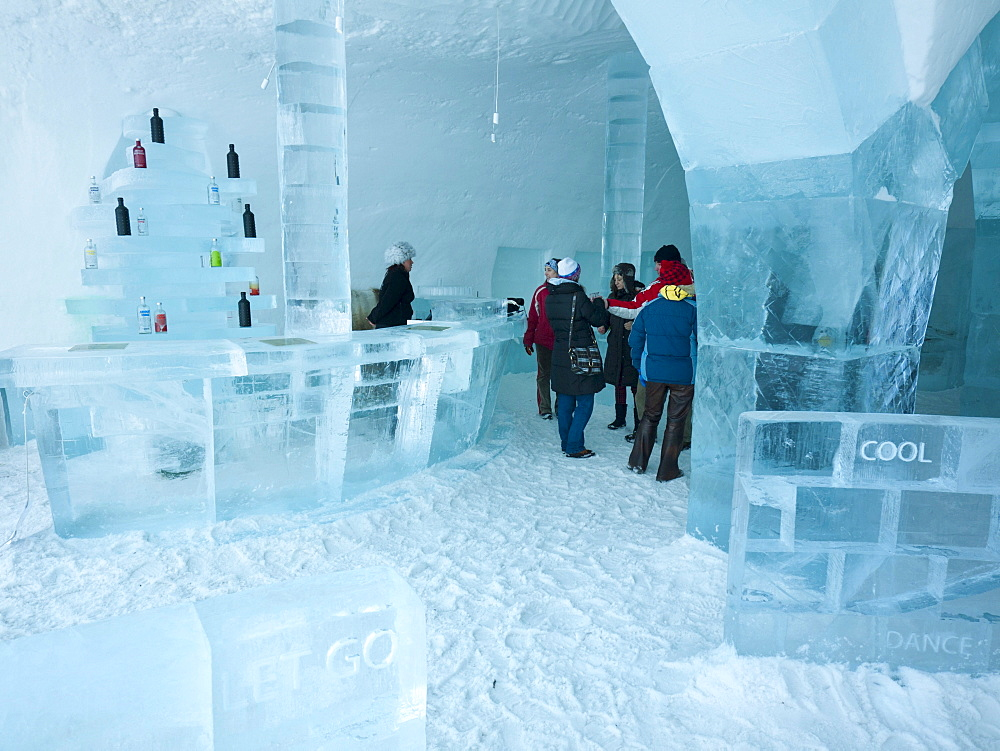 Visitors standing in the Absolut ice bar in the ice hotel in Jukkasjaervi, Kiruna, Lappland, northern Sweden, Sweden, Europe - 832-106003