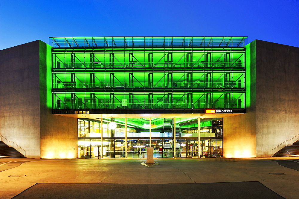 Neon-lit glass facade of the train station in Zug, Switzerland, Europe