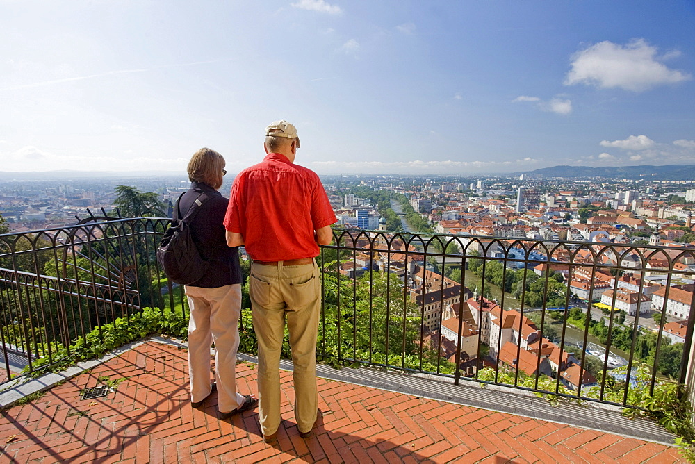 Senior couple enjoying view from Schlossberg toward historic town, Graz, Styria, Austria, Europe