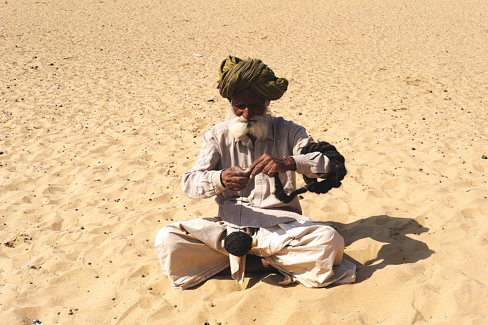 Old man spinning wool with a hand spindle, Thar Desert, Rajasthan, North India, India, Asia