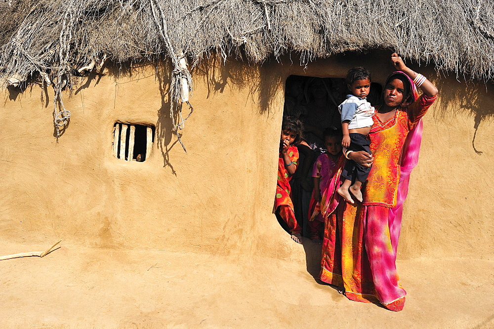 Woman in a sari with a toddler at the entrance to her house, Thar Desert, Rajasthan, North India, India, Asia