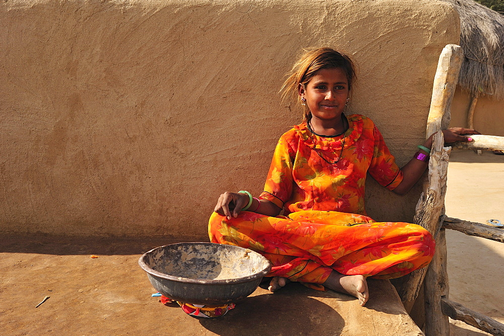 Young girl with a bowl for collecting camel dung, Thar Desert, Rajasthan, North India, India, Asia