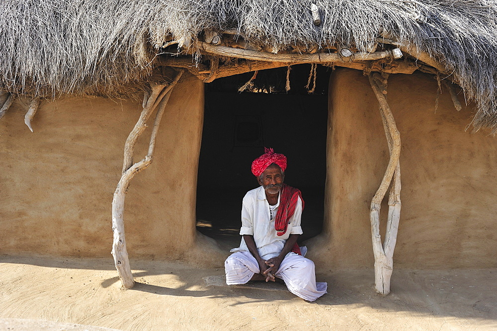 Man with turban at the front door to his house, Thar Desert, Rajasthan, North India, India, Asia