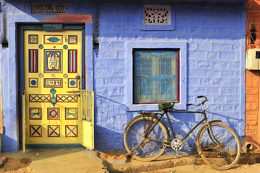 Front door decorated with ornaments and a bicycle in front of a blue wall in an Indian village, Thar Desert, Rajasthan, India, Asia