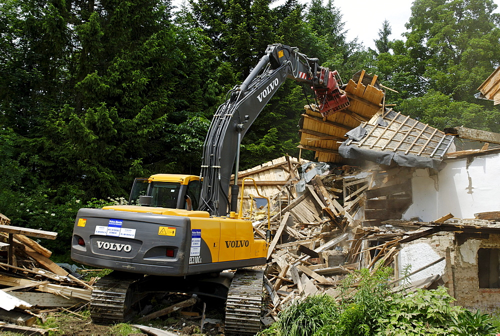 Demolition works with a digger, dismantling of a building, demolition of a house