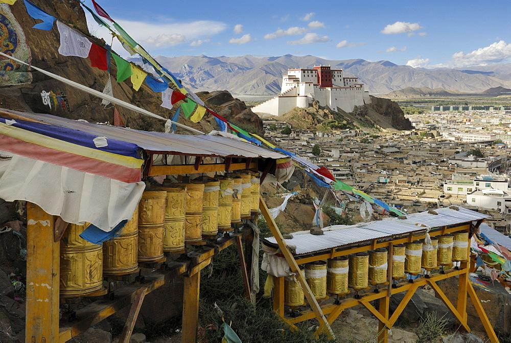 Prayer wheels, view over the historic town centre and the rebuilt Shigatse Dzong fortress, Shigatse, Tibet, China, Asia