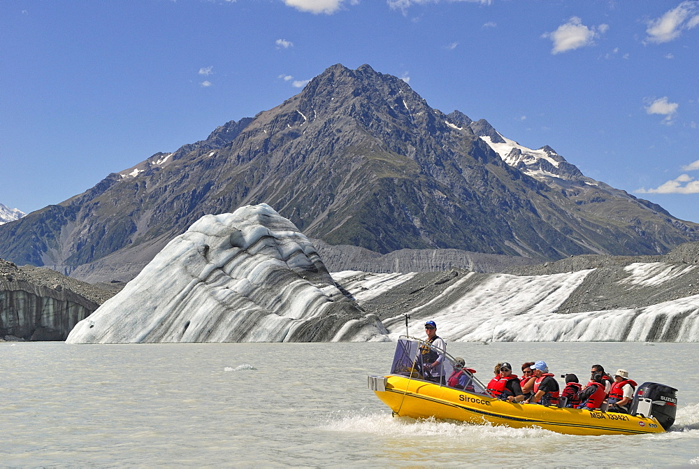 Icebergs and an excursion boat on Tasman Lake, in front of Mount Chutley, Mount Cook National Park, South Island, New Zealand