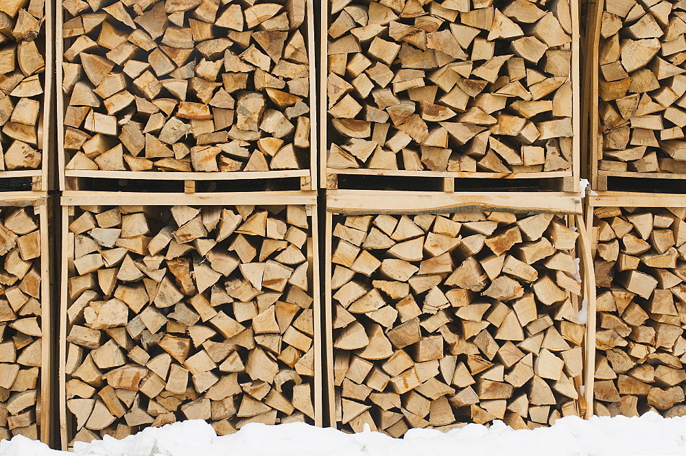 Accurately filled boxes of fire wood in the snow, timber, background