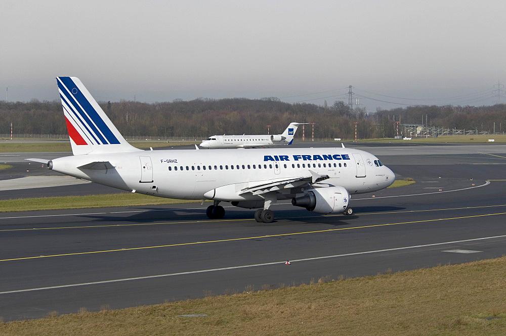 Air France Airbus A319-111 passenger jet on the runway of Duesseldorf International Airport, behind, a SAS Jet taking-off, North Rhine-Westphalia, Germany, Europe