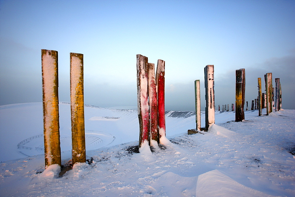 """""""Totems"""" landmark art installation created from more than 100 processed railway sleepers by Basque painter and sculptor Agustin Ibarrola, situated on snow-covered mining waste heap Halde Haniel above the pit Prosper-Haniel in winter, Bottrop, North Rhine-"""