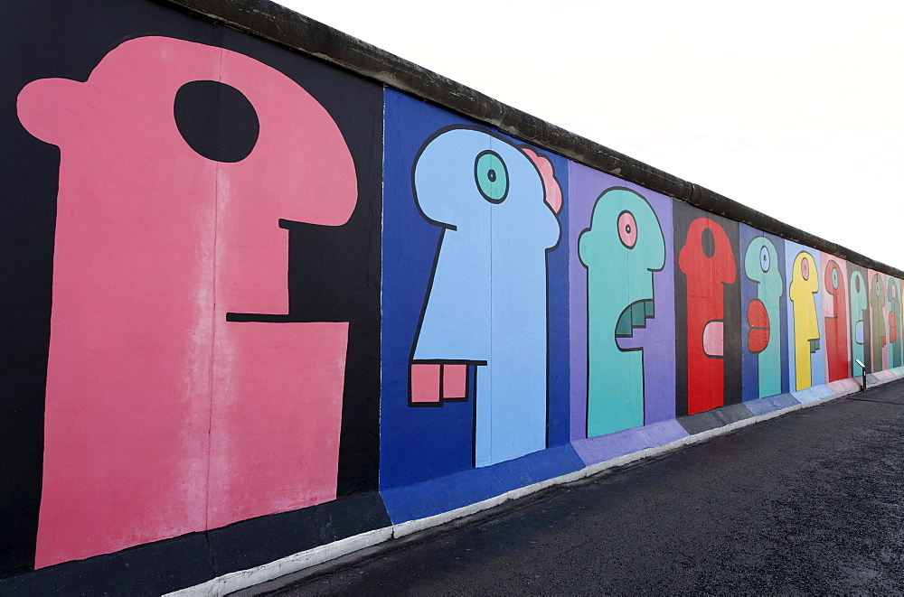Colorful heads in comic-style, painting on the remants of the Berlin Wall, East Side Gallery, Friedrichshain district, Berlin, Germany, Europe