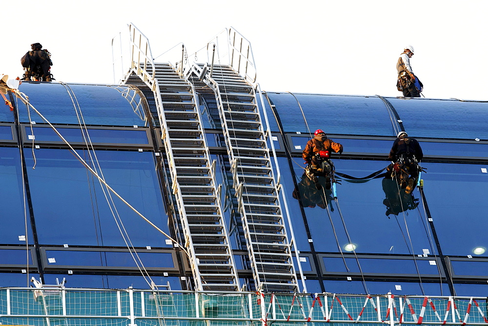 Roped up roofers mounting large glass elemtens onto a dome roof, Berlin, Germany, Europe