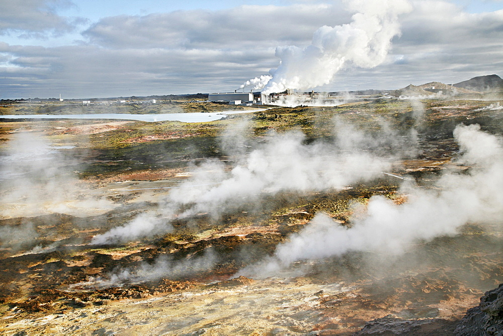 Steam from the countless holes and fractures in the earth's crust, the Solfatarten, behind it a geothermal power station and a factory for salt extraction, which is operated with geothermal energy, geothermal region of Gunnuhver, southern Iceland, Iceland - 832-11111