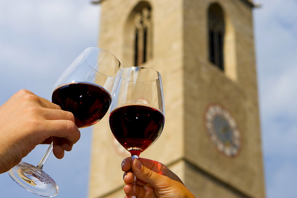 Red wine glasses clinking, steeple in Kaltern, South Tyrol, Italy, Europe