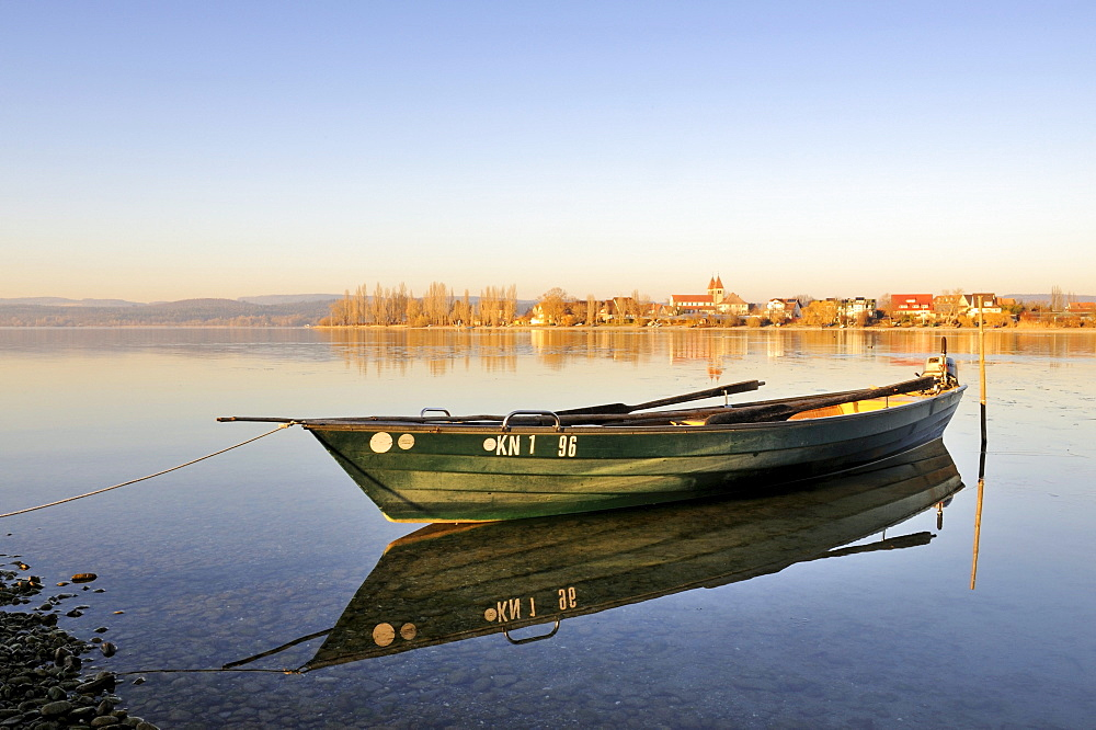 Evening mood with a fishing boat on the shore of the island of Reichenau, at the rear, the Church of St. Peter and Paul on the island area of Niederzell, Konstanz district, Baden-Wuerttemberg, Germany, Europe