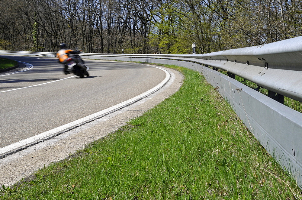 Motorcyclist in a curve on a country road with guard rail for protection, Eifel, Germany, Europe