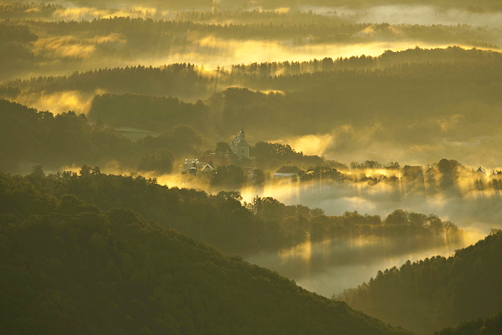 Fog in a hilly landscape with Schloss Herberstein castle in the early morning light, Kulm bei Weiz, Styria, Austria, Europe
