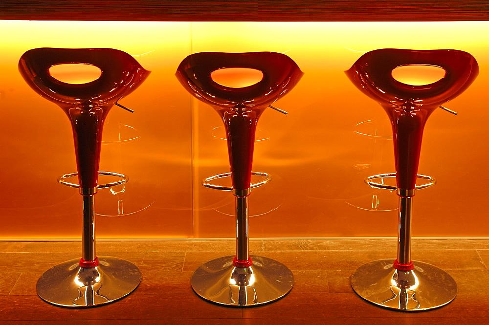 Three red plastic bar stools in front of a bar at a school of hotel management, Lycee Economique et Hotelier Joseph Storck, Rue du Chemin Noir street, Guebwiller, Gebweiler, Alsace, France, Europe