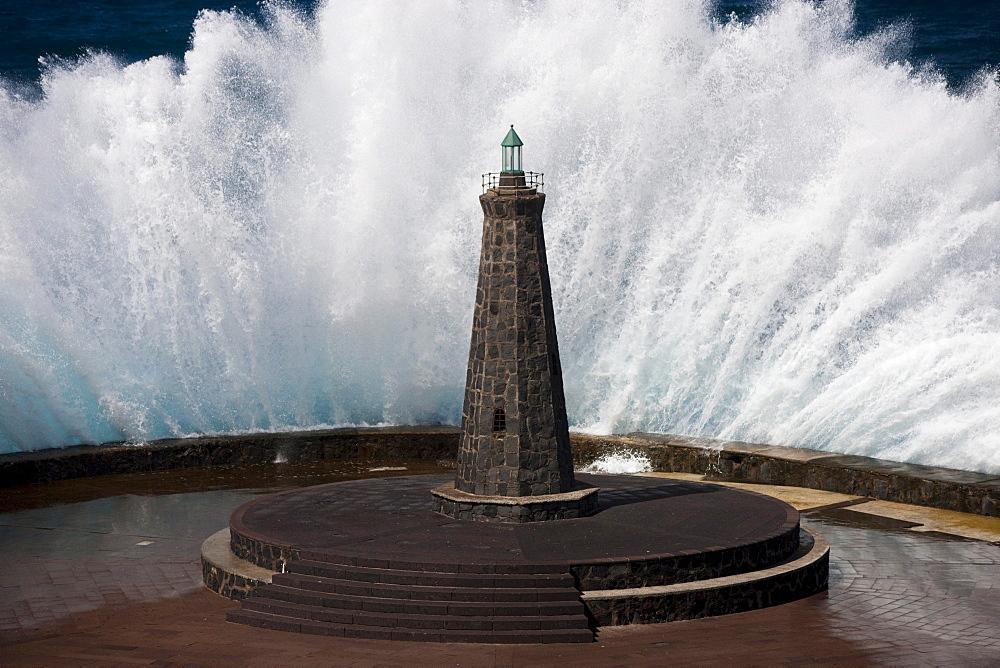 Waves behind a lighthouse on the Atlantic in Bajamar, Tenerife, Spain, Europe