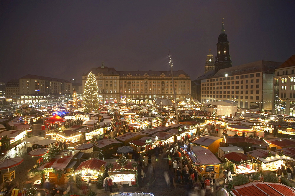 Christmas Market on Altmarkt Square with light snowfall, 575th Striezelmarkt 2009, overview with the Church of the Cross, a Christmas tree, a pyramid and a walk-through illuminated arch, Dresden, Saxony, Germany, Europe