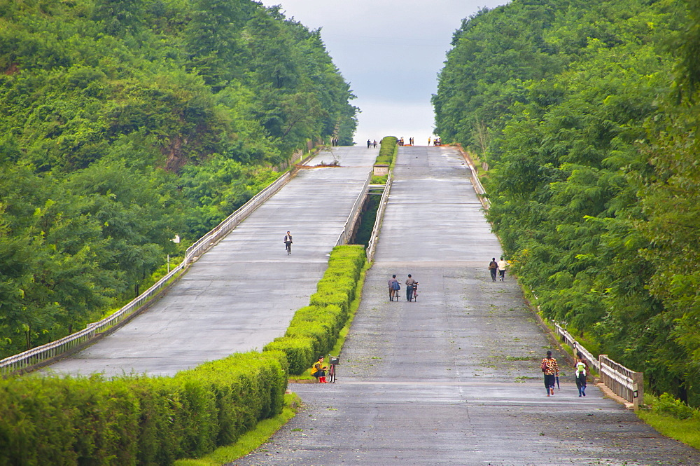 Cyclists on an empty highway, North Korea, Asia
