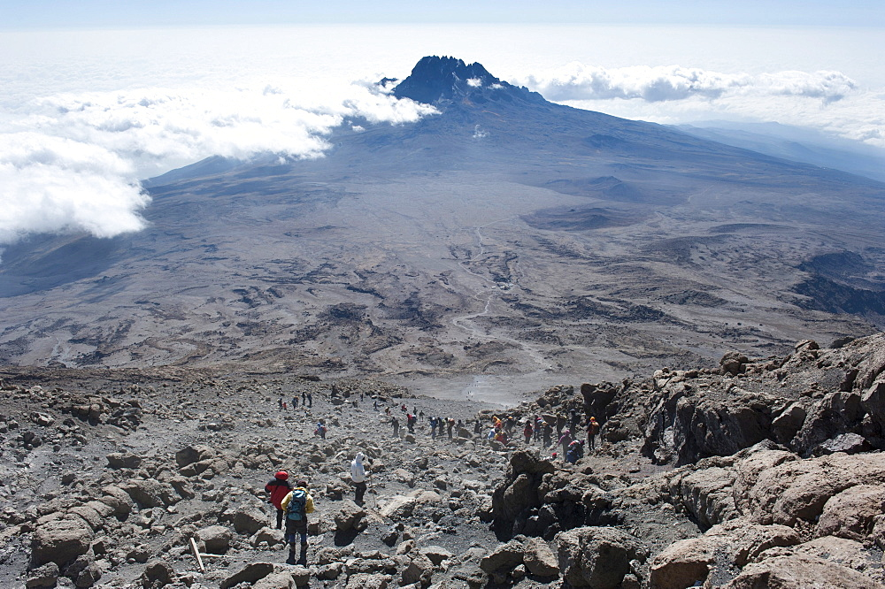 Trekking, mountain climbing, view from the crater rim towards climbers descending towards Kibo Hut at the Kibo Saddle, in the distance, the peak of Mount Mawenzi surrounded by clouds, Kilimanjaro, Marangu Route, Tanzania, East Africa, Africa