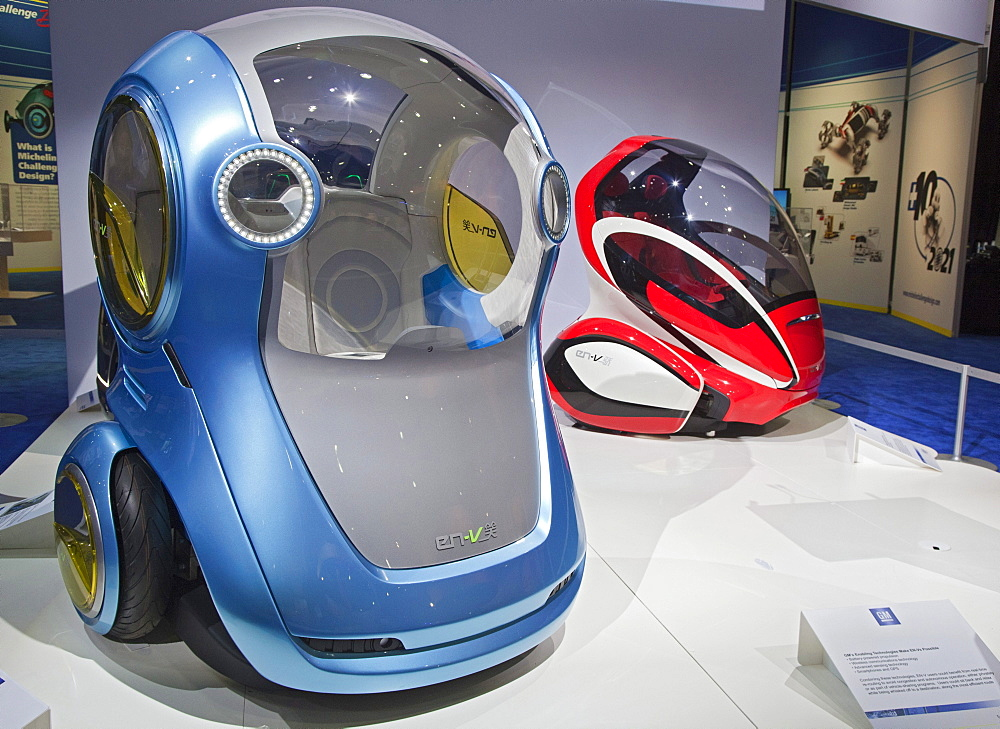 "General Motors EN-V concept vehicles; the pod-like two-passenger electric cars may someday be produced for short-range urban transportation; the blue vehicle is called Xiao, ""laugh"", and the red one is called Jiao, ""pride"", on display at the North America"