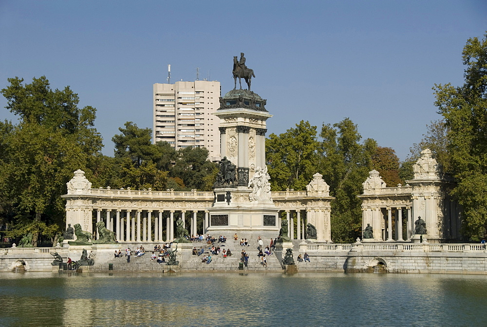 View over an artificial lake towards people in front of a monument with an equestrian statue of King Alfosno XII, Parque del Buen Retiro, Park of the Pleasant Retreat or El Retiro, Madrid, Spain, Europe