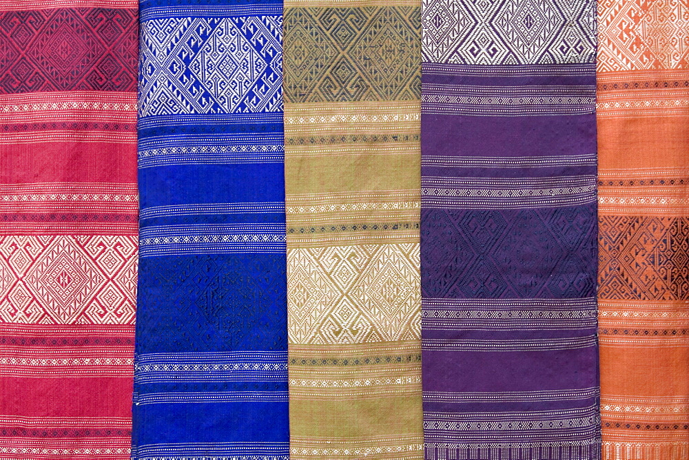 Colourful silk textiles on display at a market stall in Luang Prabang, Laos, Southeast Asia