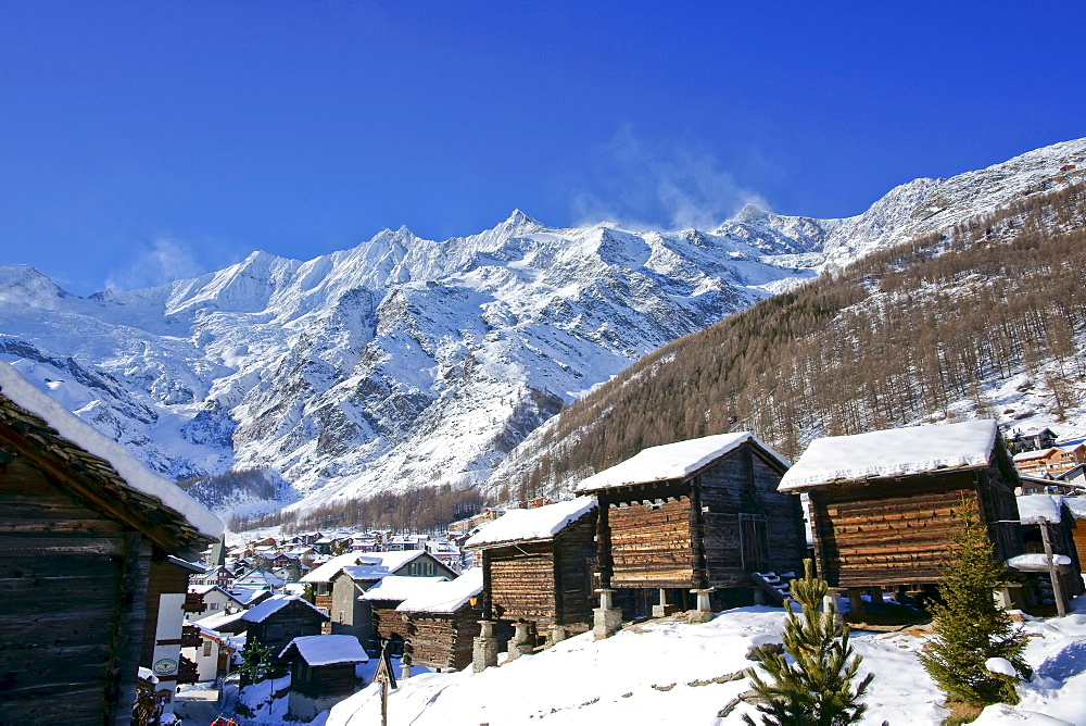 Wintry view of Saas Fee and three four-thousand-metre high mountain peaks, Taeschhorn mountain, 4491 m, Dom mountain, 4545 m, the highest mountain of Switzerland, and Lenzspitze mountain, 4264m, canton of Valais, Switzerland, Europe