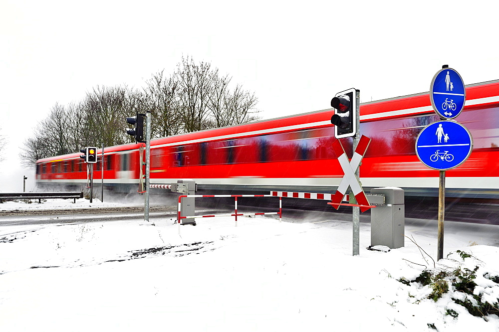 Passenger train passing a level crossing in winter, Grevenbroich, North Rhine-Westphalia, Germany, Europe