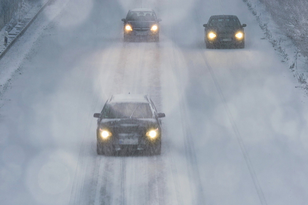 Three cars driving in a snow flulrry on a highway - 832-121563