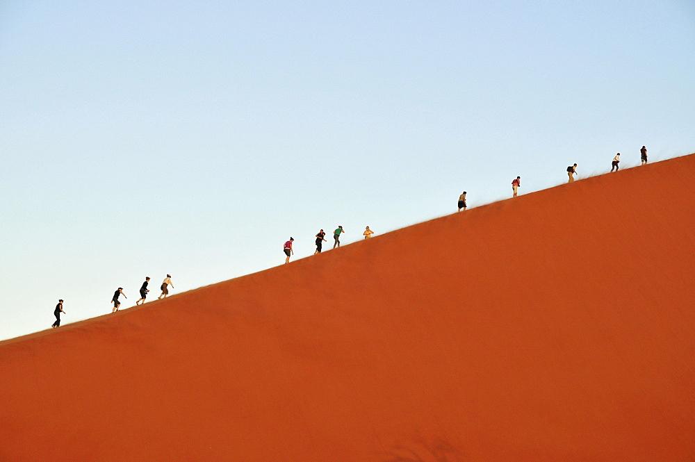 Tourists climbing Dune 45 near Sossusvlei, Namib Desert, Namib Naukluft Park, Namibia, Africa