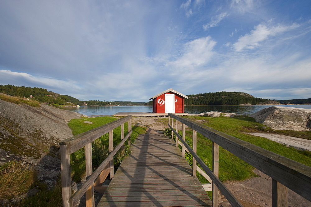 Boardwalk and red wooden hut on Badplats, Henan, Vaestragoetaland laen, Sweden, Europe