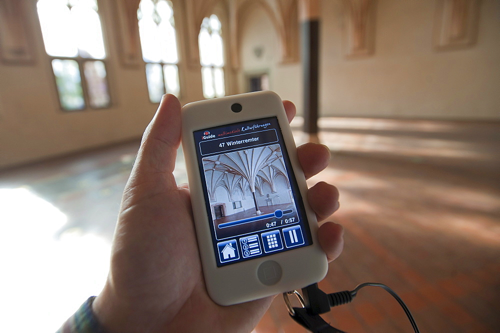 IPod held by a hand as an audio guide, Malbork Castle, Malbork, Pomerania, Poland, Europe