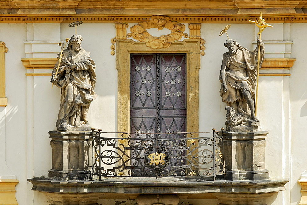 Balcony with statues of saints above the portal of Loreta Church, St. Joseph with lilies and Saint John the Baptist holding a cross and a lamb, Prague, Czech Republic, Europe